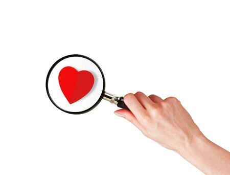 Magnifier glass in woman hand and red heart isolated on white background