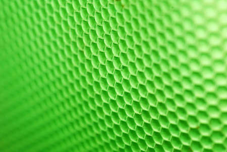marco shot of a bee hive shaped background in green