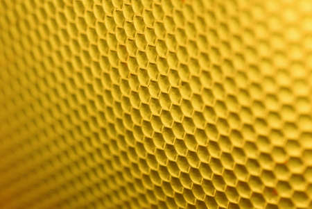 marco shot of a bee hive shaped background in yellow