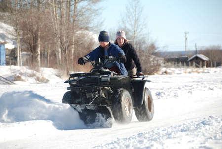 冬に雪を耕し atv に子供 写真素材