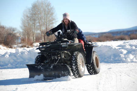 young girl is plowing snow with an atv
