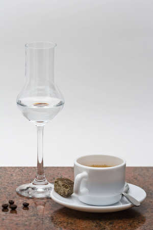 grappa: Grappa glass with espresso in cup on granitplate with espresso beans
