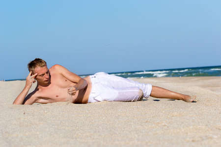white pants: A young man in white pants on the sandy beach at the beach