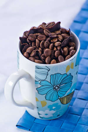a jar stand: Coffee beans with chunks of dark chocolate in a blue bowl