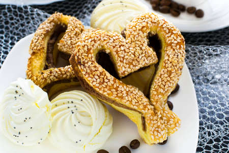 pone: heart-shaped pastry with sesame seeds, marshmallow and a cup of coffee on a silver background Stock Photo