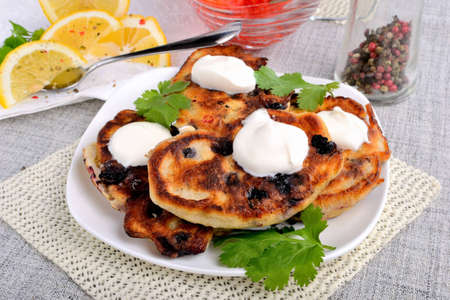 Fried pancakes with blackcurrant, sour cream and parsley, lemon wedges and red caviar Stock Photo - 12859799
