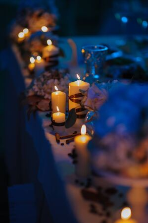 Served table for dinner on the wedding party at luxury hotel restaurantBeautiful, decorated table with flower decorations and red candles. Christmas evening or wedding party decoration. Stock Photo