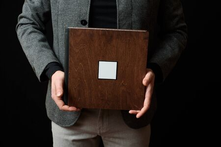 Smiling Man holds Photobooks in a wooden cover on dark background. Copy space Imagens