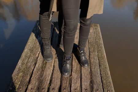 Cropped photo young legs in sneakers, married couple, husband and wife on a wooden bridge near lake. Rear view of couple standing on pier. lower half. Place for text and design. Summer in love. Stock Photo