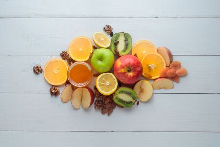 Apples, kiwi fruits, dried fruits, oranges and apples. Healthy eating concept. Shot on a white wooden table.