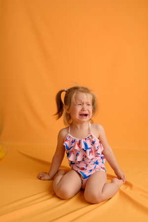 A little girl at the age of one and a half years sits on her lap and cries on a yellow background. The girl is wearing a swimsuit.