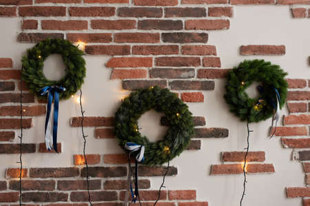 Three Christmas wreaths decorated with garlands hang on a red brick wall.
