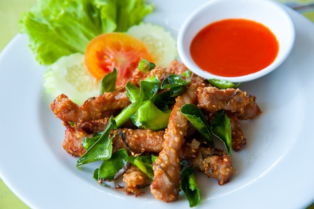 Deep fried pork with leech lime leaf and chili sauce Stock Photo