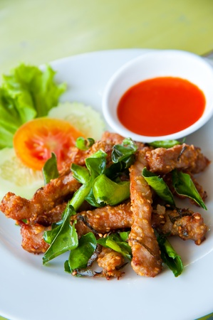 Deep fried pork with leech lime leaf and chili sauce Stock Photo