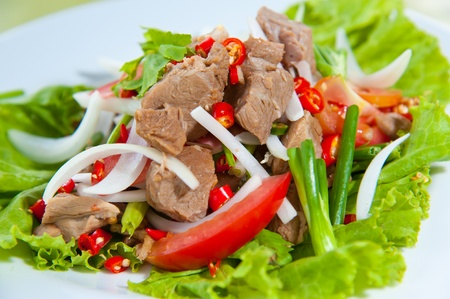 Spicy salad with pork and green herb in Thai style