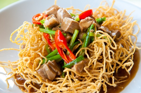 china cuisine: Chinese style deep fried yellow noodles with pork, chili, vegetables and soup