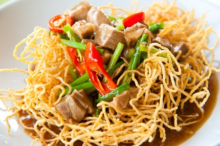 Chinese style deep fried yellow noodles with pork, chili, vegetables and soup