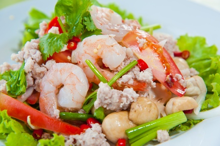 Thai dressed spicy salad with prawn, pork, green herbs and nuts : delicious food photo