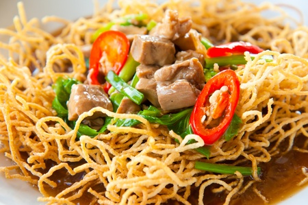 Chinese style deep fried yellow noodles with pork, chili, vegetables and soup photo