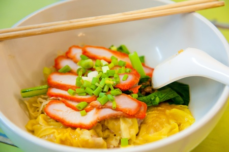 Egg chinese dry noodles with roast red pork, dumpling and vegetables photo