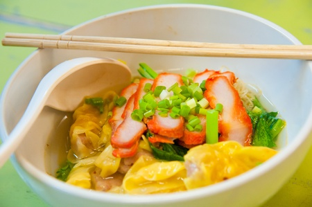 Egg chinese dry noodles with roast red pork, dumpling and vegetables Standard-Bild