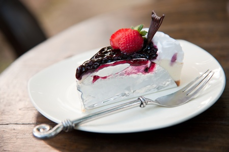 cheese cake: Piece of Blueberry Cheesecake topping with fresh strawberries on white plate closeup