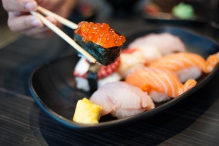 Close up of Ikura suhi in chopsticks and Variety Sushi Set on Black Dish photo