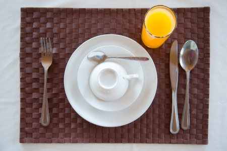 Set of breakfast tableware with a glass of orange juice photo