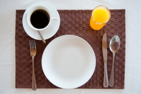 Set of breakfast tableware with orange juice and a cup of coffee photo