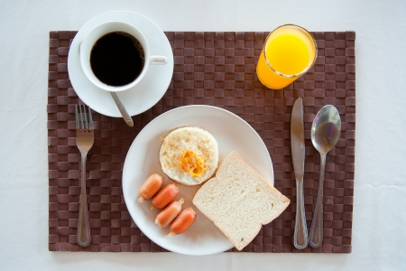 Set of breakfast   American Breakfast set with fried egg, sausages, bread, orange juice and a cup of coffee photo