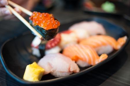 Close up of Ikura suhi in chopsticks and Variety Sushi Set on Black Dish