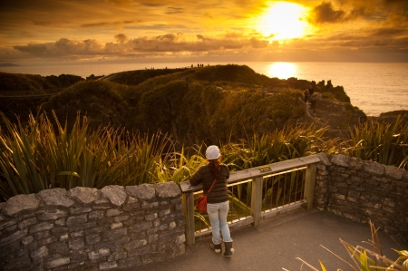 Unidentified girl look beautiful landscape of sea and pancake rock in sunset times, Pancake Rock, South Island, New Zealand Stock Photo - 17307384