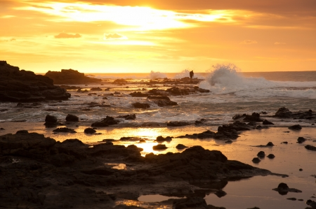 Unidentified photographer in beautiful landscape of rock and sea in sunrise time at Waikawa bay, South Island, New Zealand photo