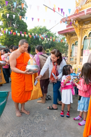 Nonthaburi, THAILAND - Jan 1, 2014    Unidentified Buddhist monks are given food offering from people in the morning for New Year Day  on January 31, 2014 in Sak Yai Temple, Nonthaburi  Thailand