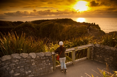 newzealand: Unidentified girl look beautiful landscape of sea and pancake rock in sunset times, Pancake Rock, South Island, New Zealand Stock Photo
