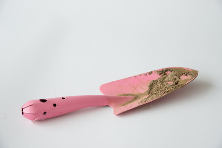 farming tools: Dirty small pink shovel on white backgrund Stock Photo