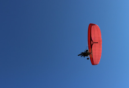 paraglider: Paraglider and a passenger on a red paraglider with a motor are flying in the blue sky.