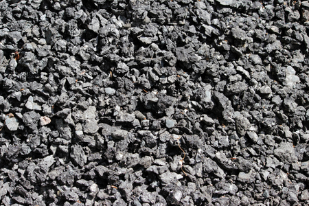 coarse-grained texture of a silvery black abrasive material from asphalt stones for wallpaper and for abstract backgrounds
