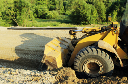 mini loader: Wheel bulldozer machine for shoveling sand at eathmoving works in construction site on a road