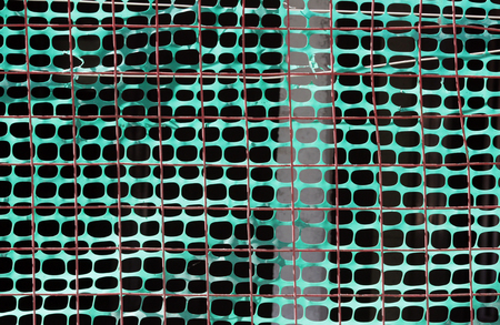 fencing of construction site with green grid on the background of orange metal fence Stock Photo