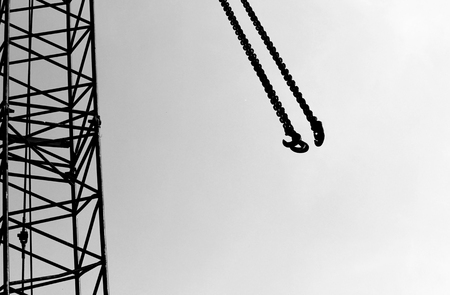 lifting hook: black and white photo hook and boom lifting machinery at a construction site on a white isolated background Stock Photo