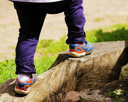 feet of a boy who climbs on the big tree stump