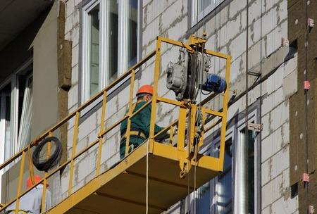 despacio: construcción suspendida cuna de color amarillo con los trabajadores en un edificio de gran altura de nueva construcción en Moscú