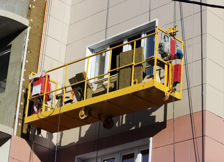 construction suspended yellow cradle without workers on a newly built high-rise building in Moscow