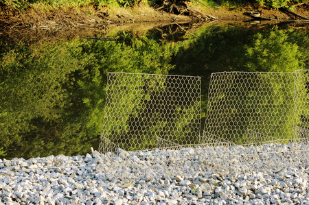 gravel roads: metal protective mesh near the canal with water protects the shedding of gravel roads. stones, gravel mound