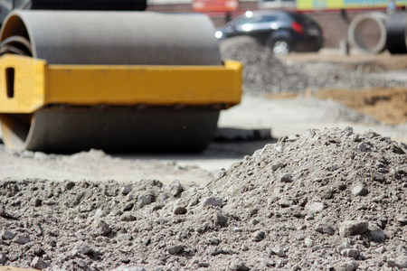 Powerful compactor compacts and levels the soil in front of the road asphalting