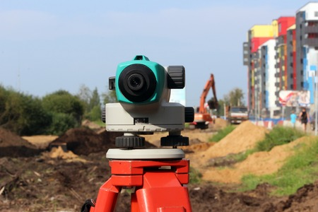 transverse: Leveler - a device for detecting the marks on the ground, the calculation of longitudinal and transverse slope, to make the construction site completely horizontal position relative to the sea level. Stock Photo