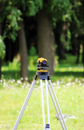 Leveler - a device for detecting the marks on the ground, the calculation of longitudinal and transverse slope, to make the construction site completely horizontal position relative to the sea level. Stock Photo
