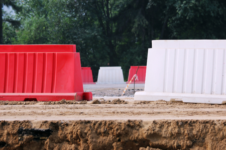 defective: Red and white plastic barriers blocking the road.
