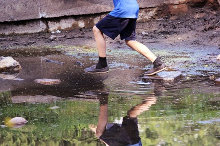 rock bottom: boy jumping from rock to rock along the bottom of a broken old fountain
